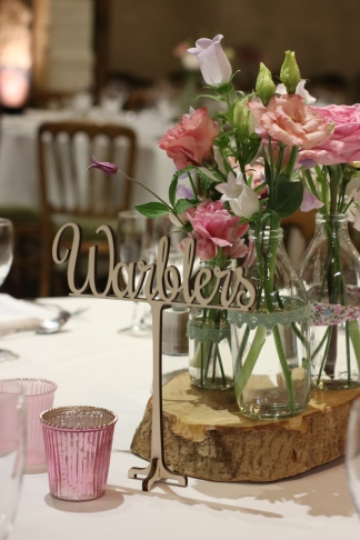 We ordered wooden laser cut table names, which looked beautiful with smokey glass candle votives and log slices for our table centres